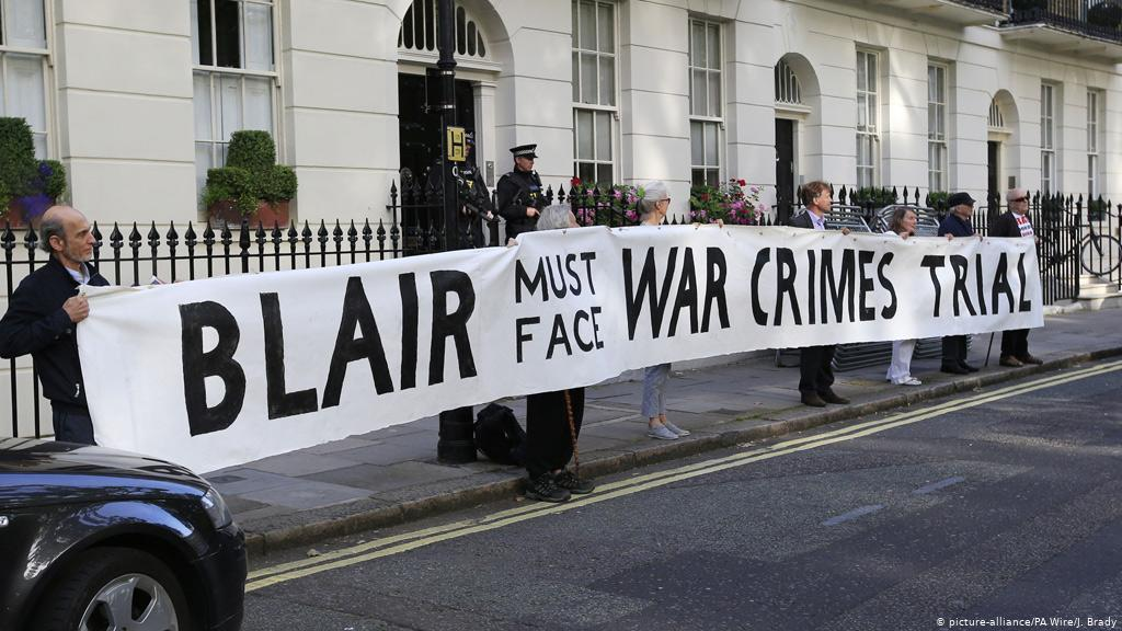 Manifestantes com faixa pedem o julgamento de Tony Blair por crimes de guerra no Iraque e Afeganistão
