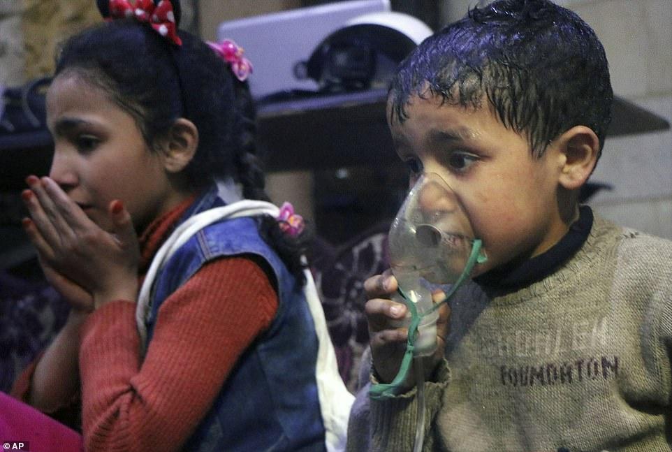 Crianças usando máscaras para inalar oxigênio, após suposto ataque com gases químicos em Douma, Síria.. A foto foi obtida pela Defesa Civil Síria-Capacetes Brancos, grupo fundado por James Le Mesurier, que tinha vínculos com extremistas jihadistas.