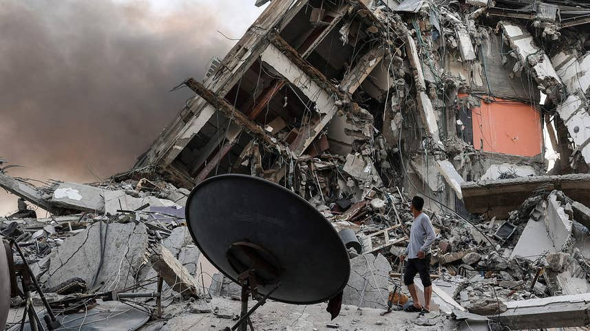 Rescuers and people gather in front of the debris of Al-Sharouk tower that collapsed after being hit by an Israeli air strike, in Gaza City