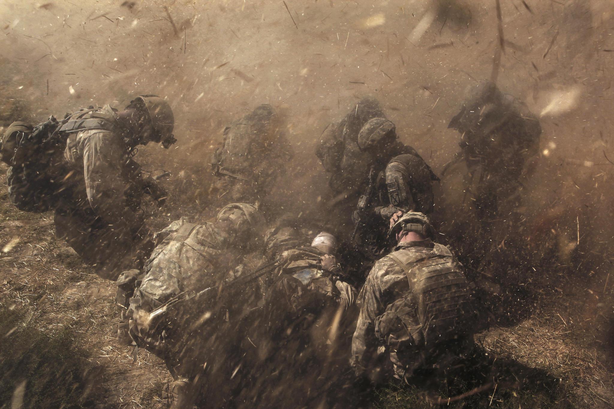 Soldados norte-americanos da infantaria atendem colega ferido