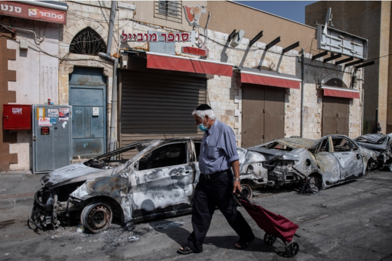 A man passes by cars torched after a night of violence between palestinians and israelis in Arab-Jewish town of Lod, central Israel, May 11, 2021.