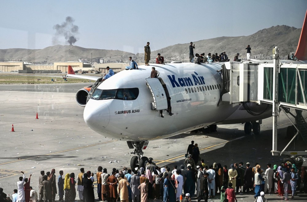 People climb atop a plane at Kabul airport on Aug. 16. Thousands of people mobbed the airport trying to flee as Afghanistan fell to the Taliban. WAKIL KOHSAR/AFP VIA GETTY IMAGES