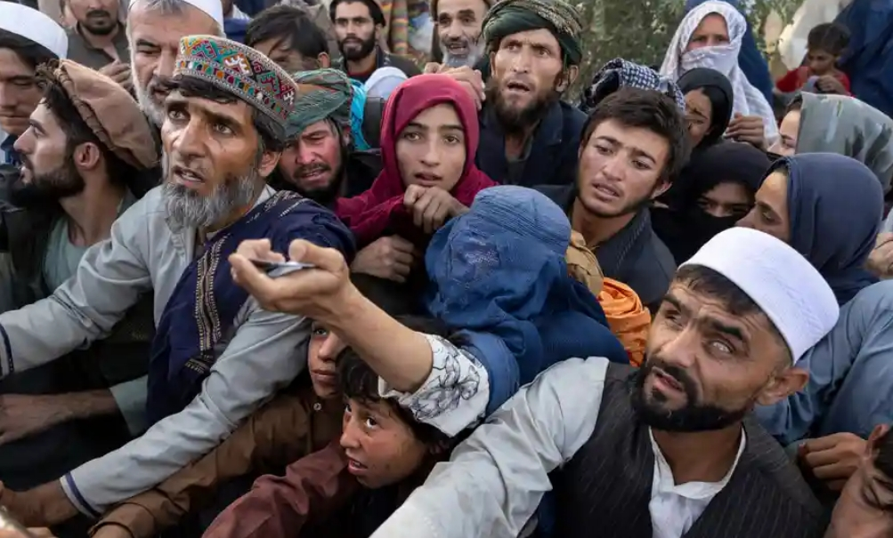 Displaced Afghans who have fled the advancing Taliban reach out for aid at a camp in Kabul, Afghanistan. Photograph: Paula Bronstein/Getty Images